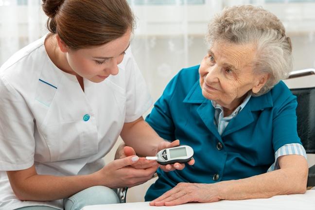 pielęgniarka pomaga starszej pani w wykonaniu pomiaru cukru glukometrem